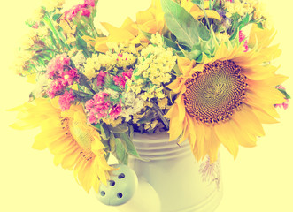 Yellow sunflowers and colored wild flowers in a white sprinkler