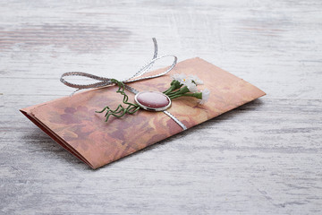 Handmade wedding invitations made of paper pver wooden vintage background