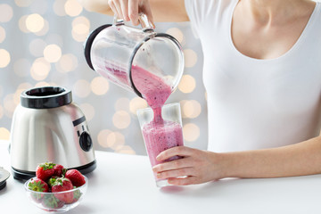 close up of woman with blender pouring milk shake