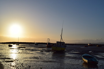 Sunset with boats at low tide