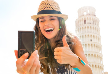 Happy woman tourist giving thumbs up taking selfie in Pisa
