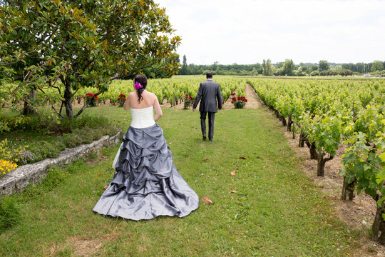 A newly wed couple walking through a vineyard