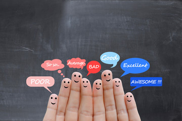 Customer satisfaction scale and testimonials concept with happy human fingers on a blackboard