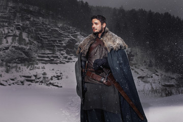 Medieval knight with sword in armor in winter rock landscape