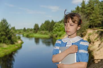 Девочка на берегу реки с планшетом.