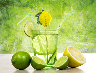 lime and lemon cocktail over green background