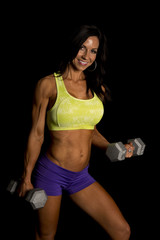 woman blue shorts and green sports bra on black curl smile