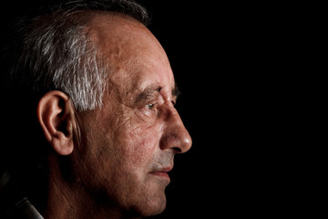 Profile of a senior man on black background, Side view