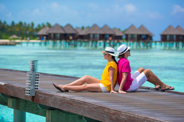 Young couple on beach jetty near water villa in honeymoon
