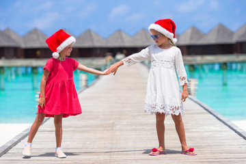Little adorable girls in Santa hats during beach vacation at