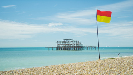 West Pier at Brighton beach with a lifeguard flag in the foreground
