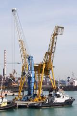 Piombino, Italy -Cranes and moored boats in the Industrial Port of Piombino