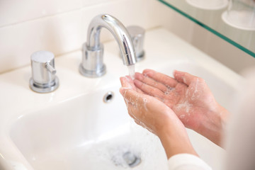 Washing hands with soap under running water, woman hands