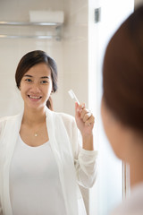 Asian young woman will brushing her teeth happily