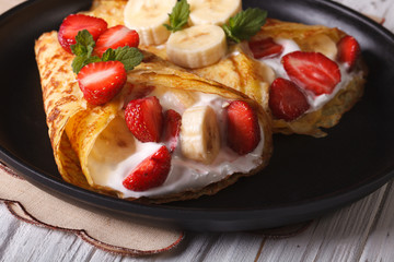 pancakes with fresh strawberries, bananas and cream close-up