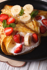 crepes with strawberries, bananas and cream close-up.  Vertical