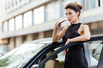 Attractive girl standing near the car