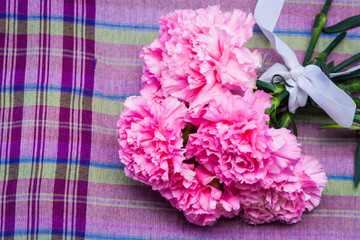 pink carnation floral on violate cloth background