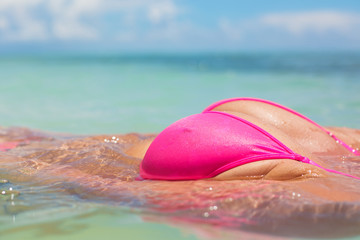 Woman in pink bikini swimming in ocean