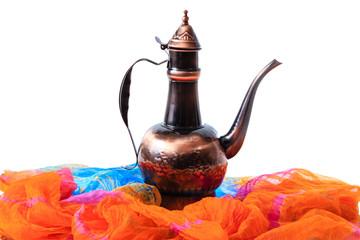 Eastern jug on a orange draped cloth
