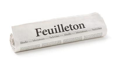 Zeitungsrolle mit der Überschrift Feuilleton