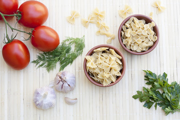 Pasta in a clay pot, tomatoes, herbs and spices on light makisu