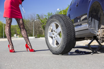 Sexually dressed female mechanic body. Lady dressed in provocative clubbing pantyhose and bright red shoes high heels mini skirt rolls large wheel to car fixed on jack-screw with some tools