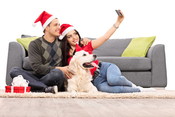 Young couple with Santa hats taking a selfie