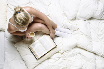 Young girl reading in bed