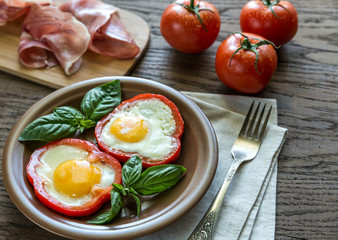 Fried eggs with prosciutto on the wooden table