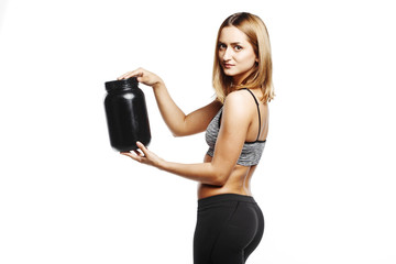 pretty fitness girl holding jar of sports nutrition