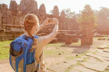 Female tourist with smartphone taking picture in Angkor Thom