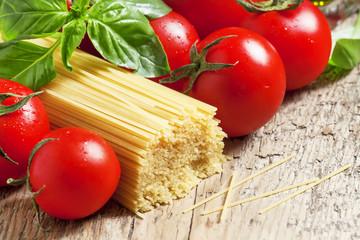 Dry Italian pasta Capellini with tomato and basil, selective foc