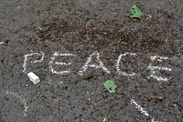Inscription on asphalt with white chalk: peace