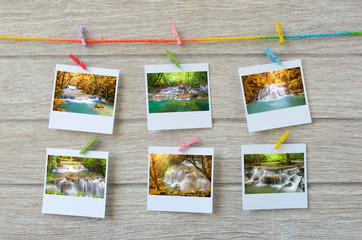 waterfall photos hanging with clothespins on wooden background