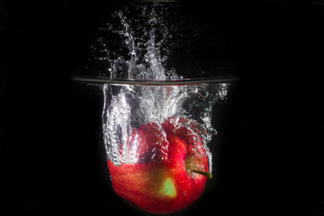 Apple in water on a black background
