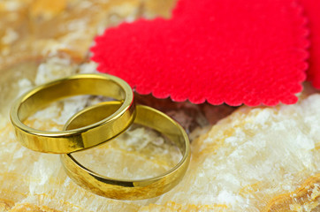 couple of gold rings on marble stone background