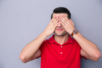 Casual man covering his eyes with fingers