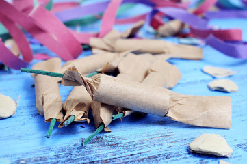 streamers, confetti and firecrackers on a rustic blue wooden sur