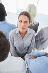 Unhappy businessman looking at camera with her colleagues