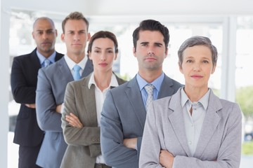 Business people standing in a row arms crossed