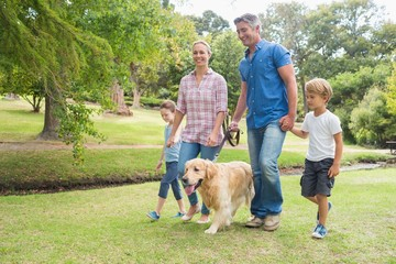Happy family in the park with their dog