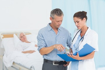 Doctor explaining report to female patient and husband