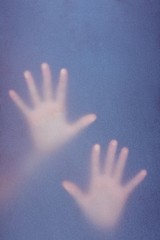 Hands touching frosted glass
