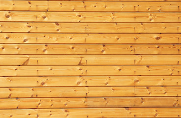Background texture of finely slatted natural brown pine wood in a parallel pattern