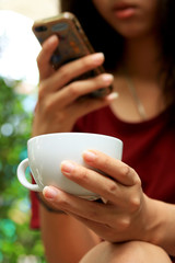 Blurred woman using smart phones and coffee.
