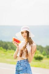 Gorgeous bohemian fashion girl with watermelon slice