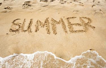 """""""Summer"""" handwritten on wet sand at seashore"""