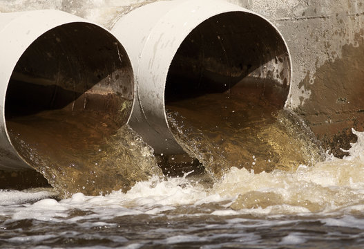 Toxic covid coronavirus water running from a sewer to the river