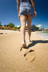 Closeup of woman leaving footprints on sandy beach